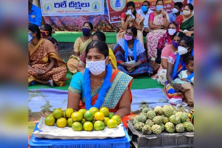 A teacher protesting in Guntur by selling oranges and custard apple