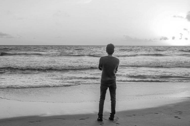 Representative image of teenage boy standing in beach