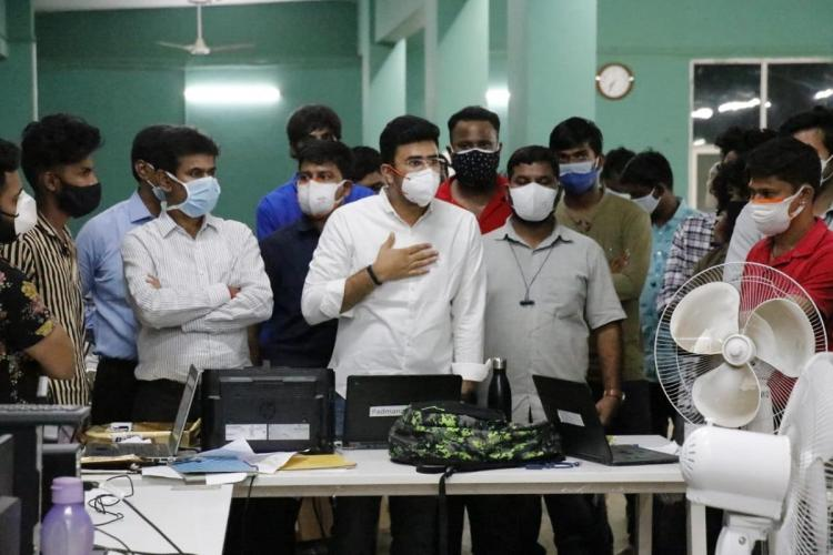 Tejasvi Surya in a white shirt and white mask with his hand on his chest speaking with BBMP War Room staff members