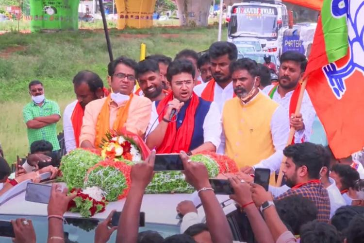 Tejasvi Surya talking into a mic from the open sunroof of a vehicle. He is surrounded by a group of supporters.