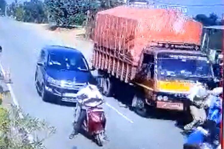 A truck can be seen driving into a crowd in Telangana A police officer is seen in the crowd of onlookers at an accident spot A two-wheeler and Innova are seen in the screenshot
