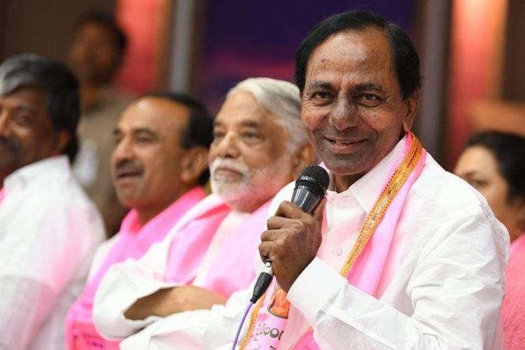 Telangana Chief Minister K Chandrasekhar Rao seated and speaking into a mic with a smile while his party colleagues are seen in the background He is wearing a white shirt and a pink shawl around his neck