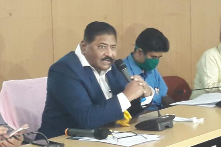 Telangana Election Commissioner C Partha Sarathi seated and speaking into a mic. He is wearing a white shirt and dark blue jacket. A couple of other officials can be seen seated beside him.