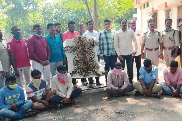 A photo of the accused seated on the ground along with the seized Leopard skin and the police team