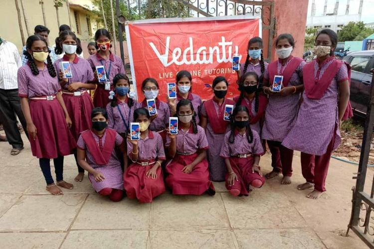 Telangana social welfare school students holding smartphones they received from Vedantu for online classes the girls are wearing their school uniform and standing in front of a banner that reads Vedantu