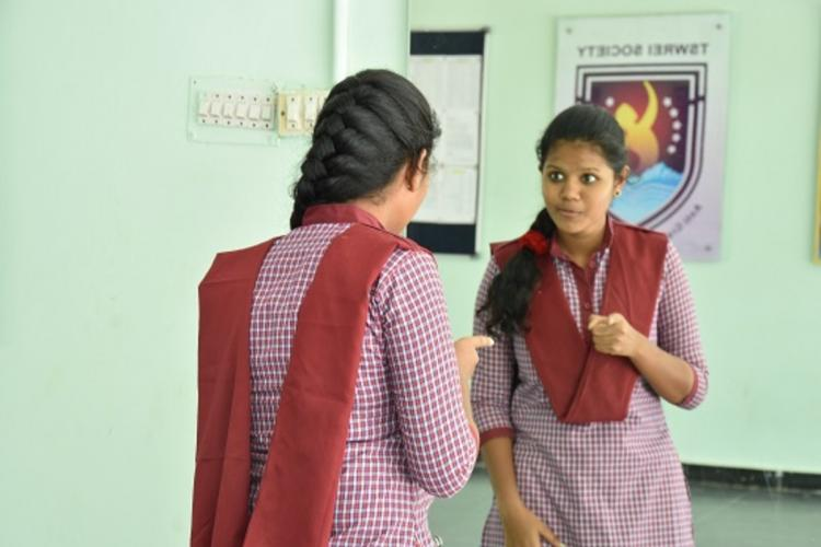 A young girl student of Telangana Social Welfare Residential Educational Institutions Society speaking into a mirror