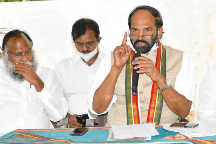 Telangana Congress leader Uttam Kumar Reddy talking to media with a mic and two other persons by wearing a tri coloured shawl