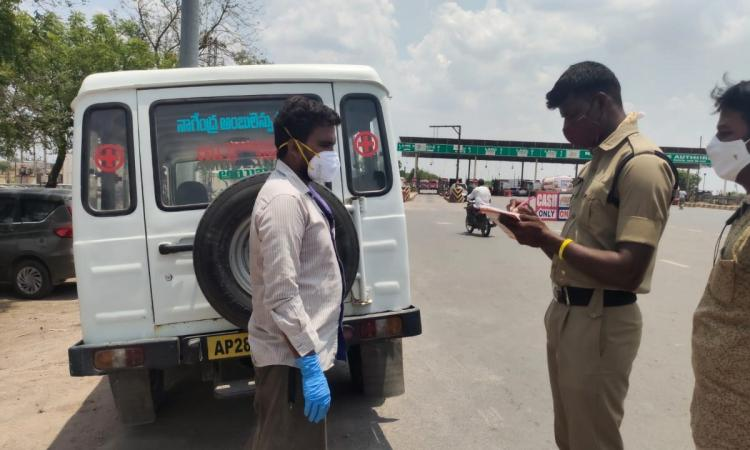 A police officer noting down the details given by the ambulance driver