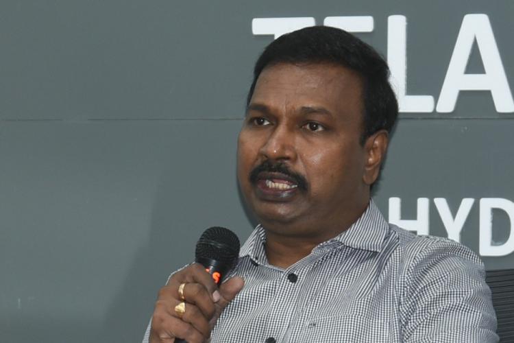 Dr Srinivasa Rao holding a mic and addressing the media