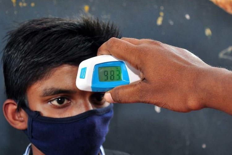 A student in Kerala being screened for temperature