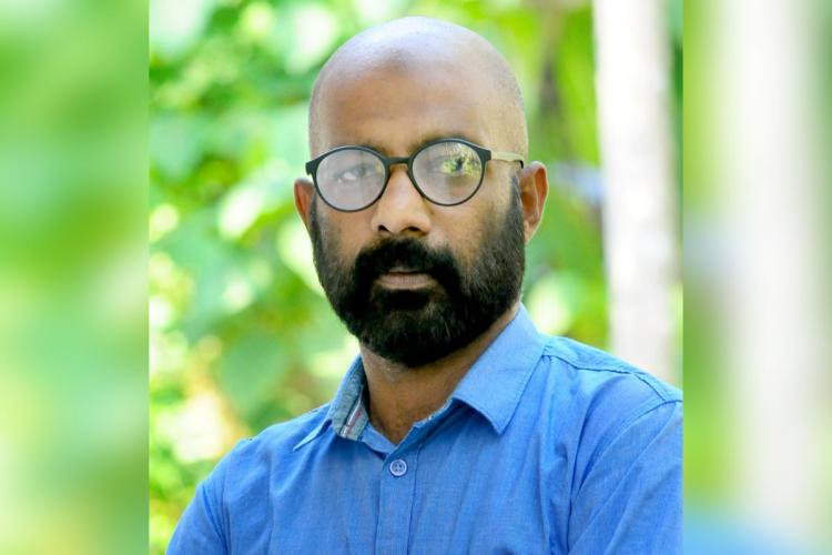 Kannur native VK Thajudheen who was wrongfully arrested for chain-snatching in a blue shirt and glasses