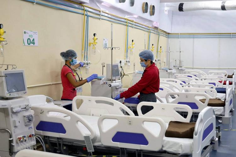 Health workers standing by an empty bed in a COVID-19 hospitall in Thane