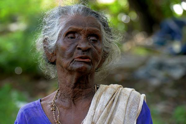 In Kerala this old woman tries vainly to keep an old pond bed garbage free