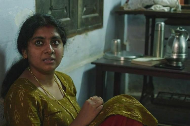 Nimisha Sajayan wearing a green kurta and sitting on the floor in The Great Indian Kitchen