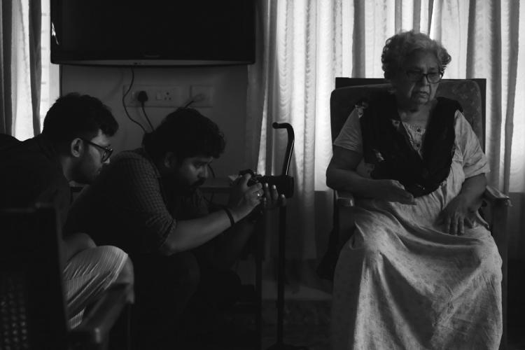 An elderly woman sits on a chair as two young men kneel besides her, shooting her on a camera, in this black and white picture