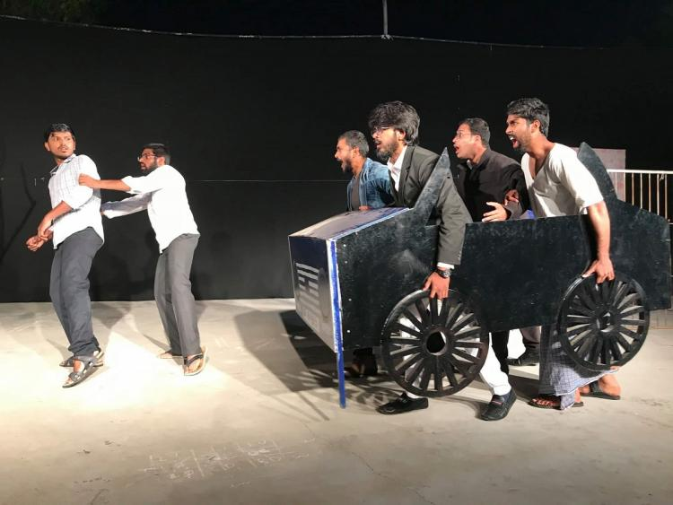 Theatre artists performing a play with props