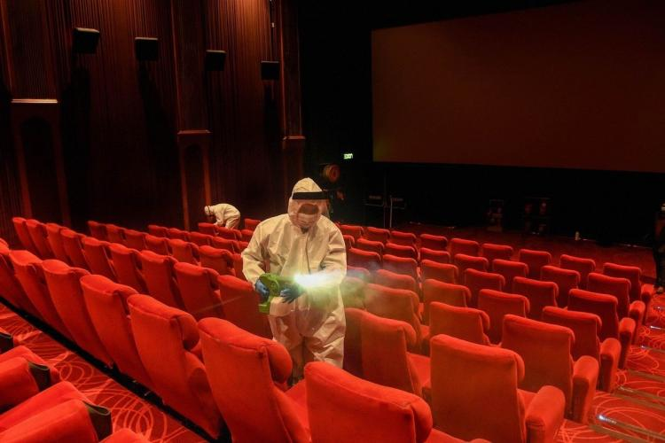 Two men in PPE kits sanitising a theatre The empty seats are red in colour