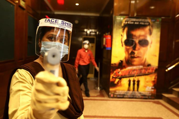 Workers wear facemasks and face shields inside a theatre during a sanitisation work ahead of the scheduled reopening of cinema theatres