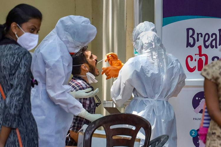 Two health workers in white PPE kits take sample from a young man as another young woman wearing mask stands beside them