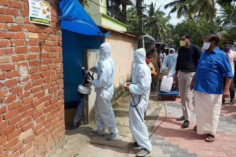 Two health workers in personal protective equipment spraying sanitisers in a residential colony A few officials of Thiruvananthapuram corporation are also present