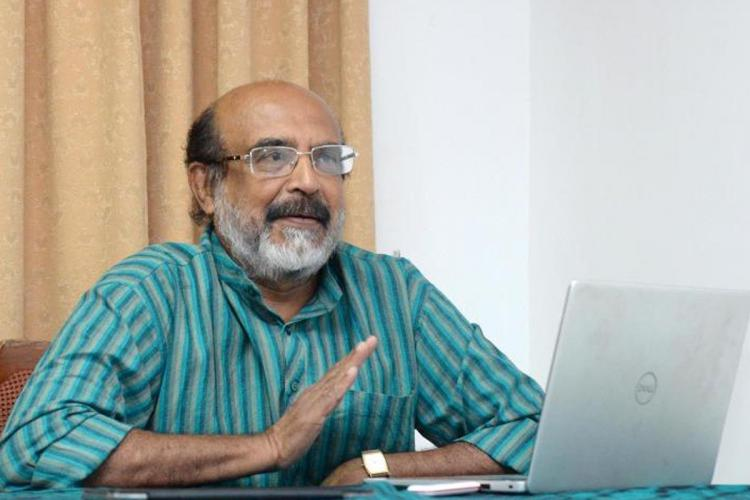 Kerala Finance Minister Thomas Isaac on his desk He is sitting in front of an open laptop