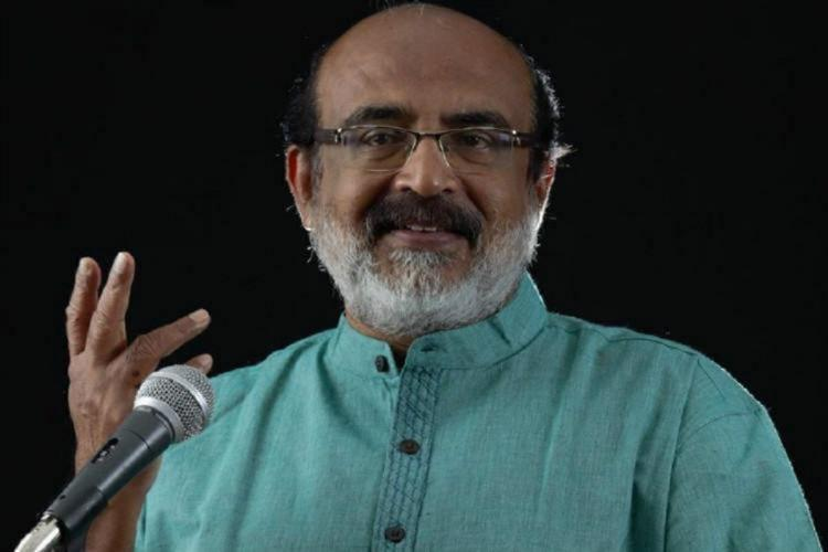 Thomas Isaac in a green kurtha, with a hand raised in a gesture, smiles, in front of a microphone, against a black background