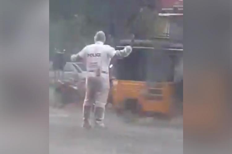 Traffic constable Muthuraja regulating traffic in Thoothukudi during heavy downpour He is wearing a transparent raincoat over his uniform
