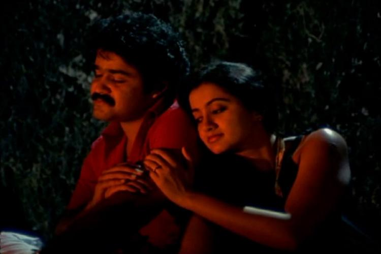 Mohanlal and Sumalatha sit in the dark in a still from Thoovanathumbikal