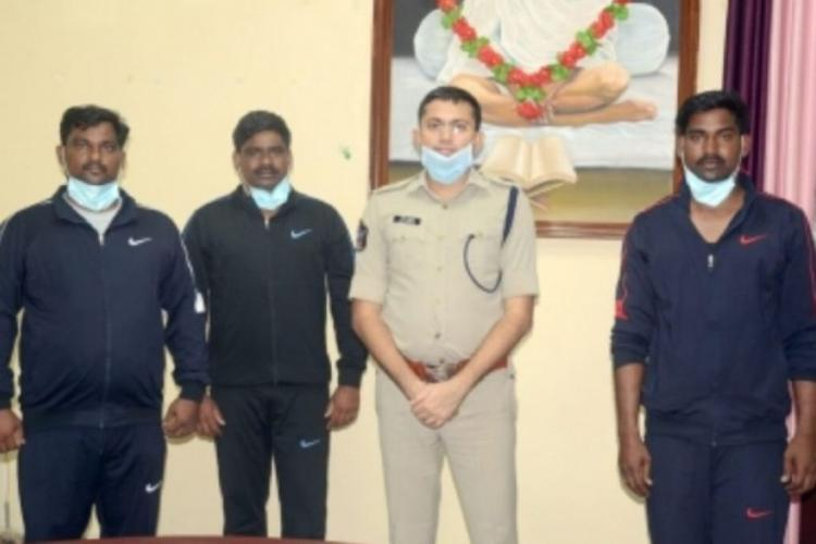 Three men from Andhra Pradesh posing with police after they were rescued from a kidnapping gang and returned to India
