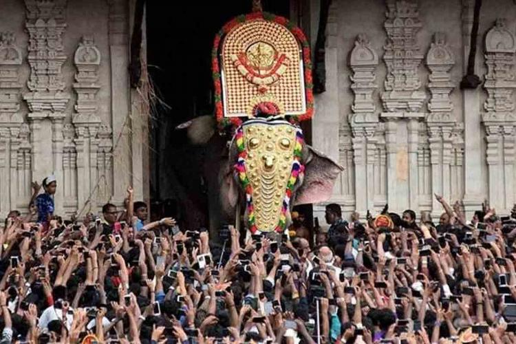 Thousands of people crowd around a caparisoned elephant exiting a temple