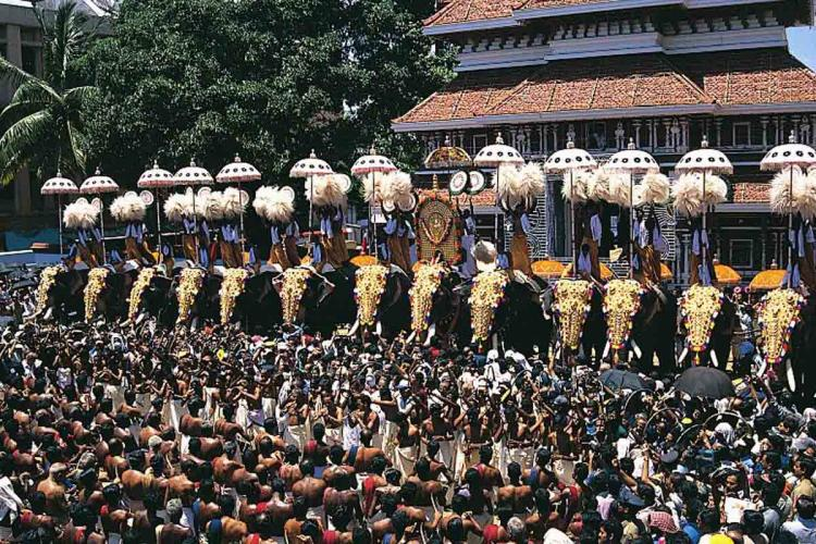 Thousands of people seeing elephants paraded with umbrellas and decoration
