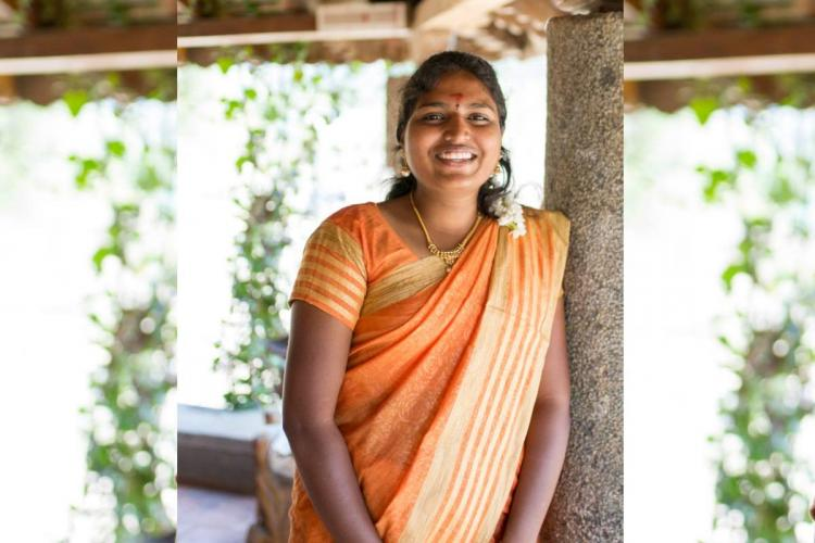 Ponmani smiling in an orange saree leaning against a pillar