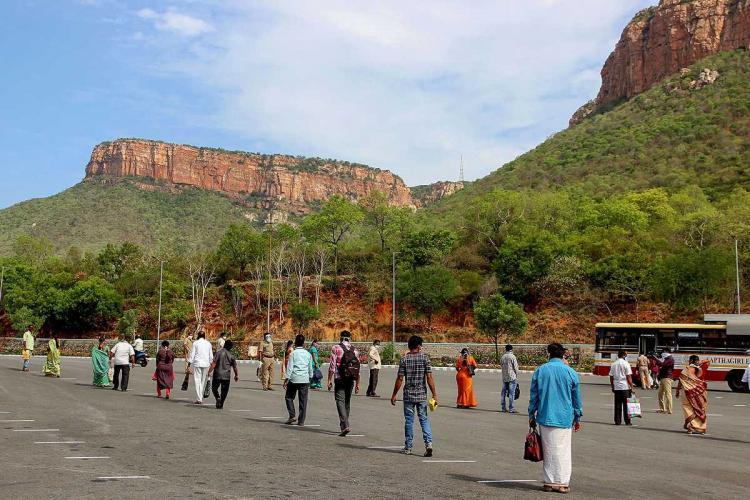 Employees queue to board a bus at foothill of Lord Venkateswara temple at Tirumala