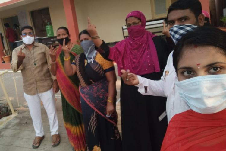 Voters in Tirupati holding up inked fingers after voting