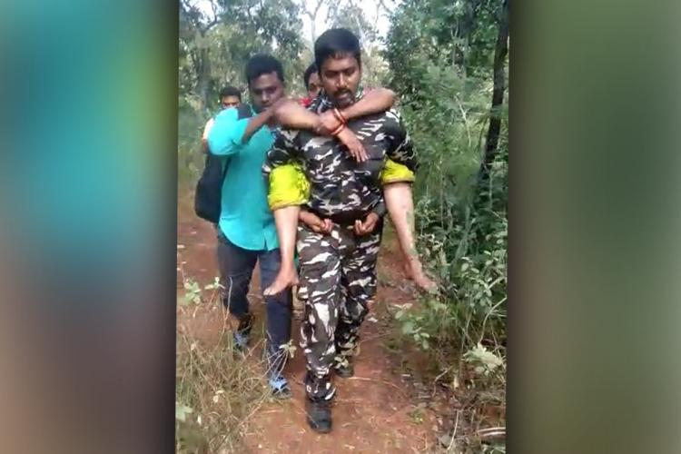 Constable Sheikh Arshad in Tirumala carrying an elderly woman on his shoulders and trekking Arshad is in uniform Woman is in a yellow saree and a man in a blue shirt walks along