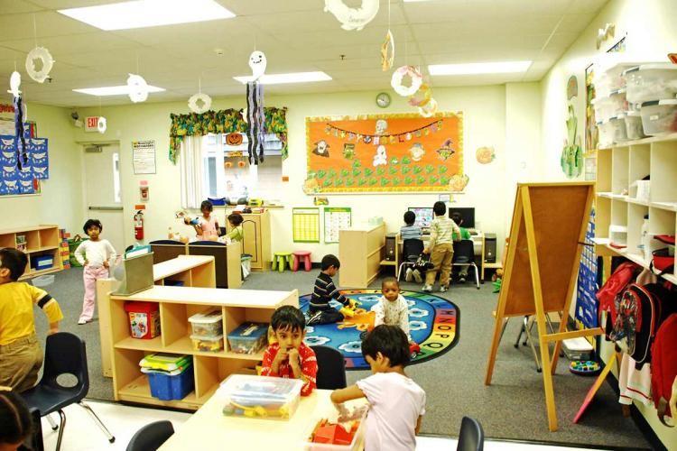 Toddlers playing in a classroom with an easel desks chairs and bags