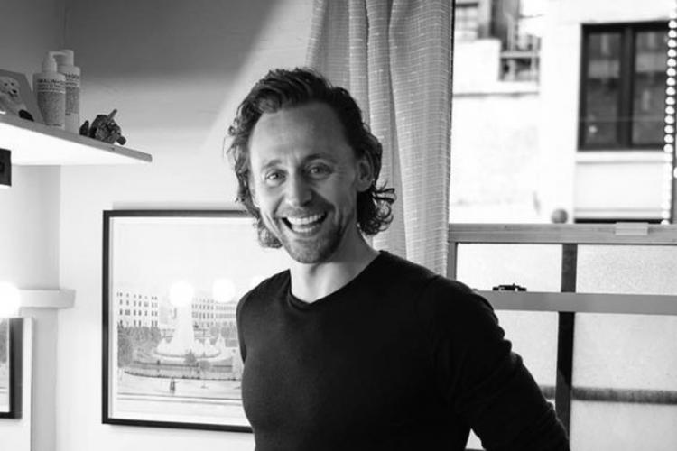 A black and white photo of Tom Hiddleston standing in a kitchen and laughing
