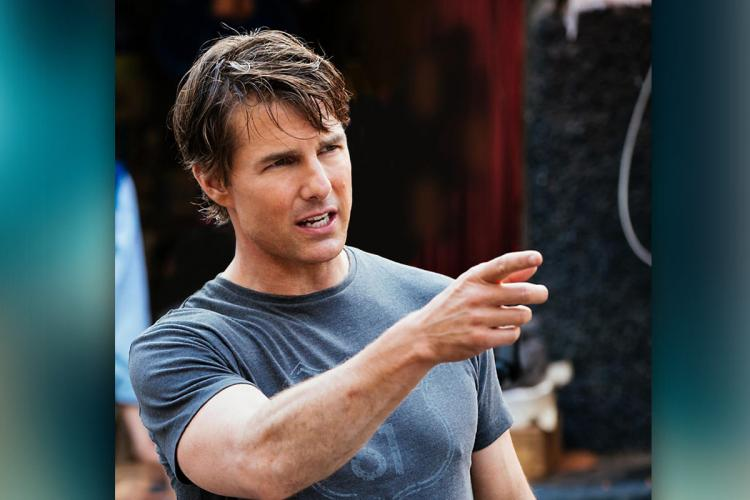 Hollywood actor Tom Cruise wearing a blue tshirt and pointing at something