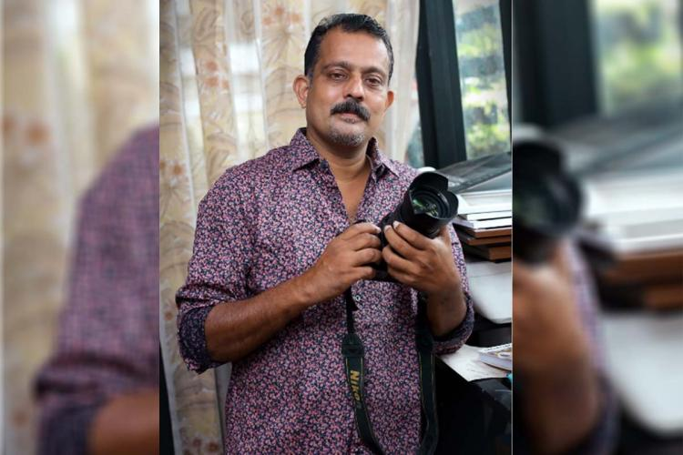 Tomy Thomas a photographer based in Ernakulam Wearing a floral printed shirt he is standing looking straight carrying a camera in his hand