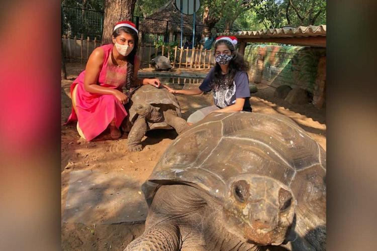 Two women in christmas caps positing with the giant tortoises