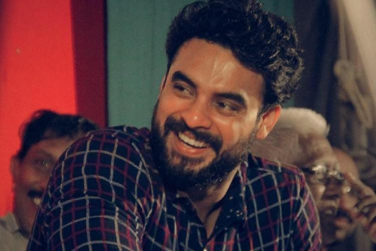 Tovino Thomas is seen in a checked shirt