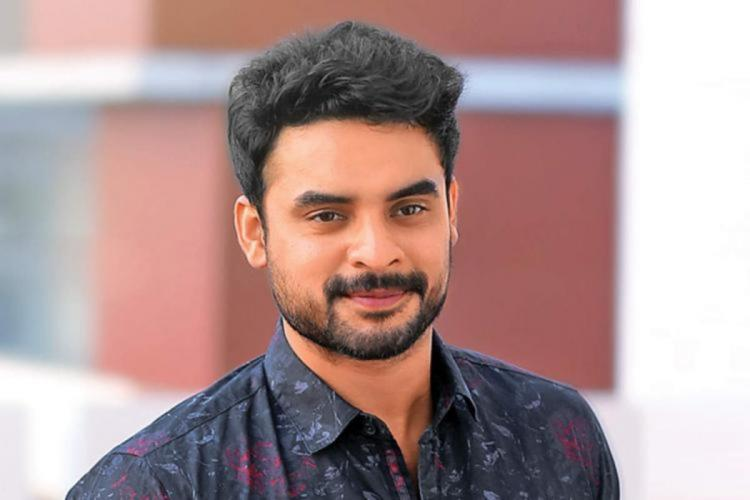 Tovino Thomas is seen in a purple shirt in the image
