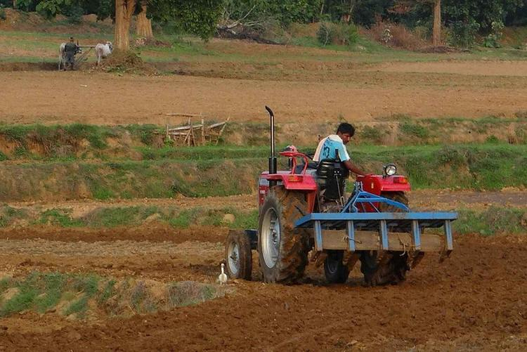 a person tilling uding a tractor