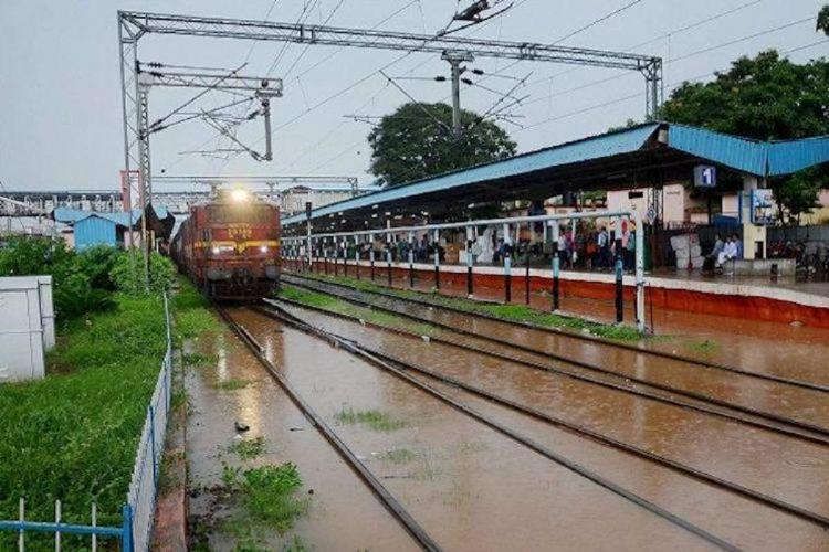 A train with its headlight on is arriving at a station that is wet from rains