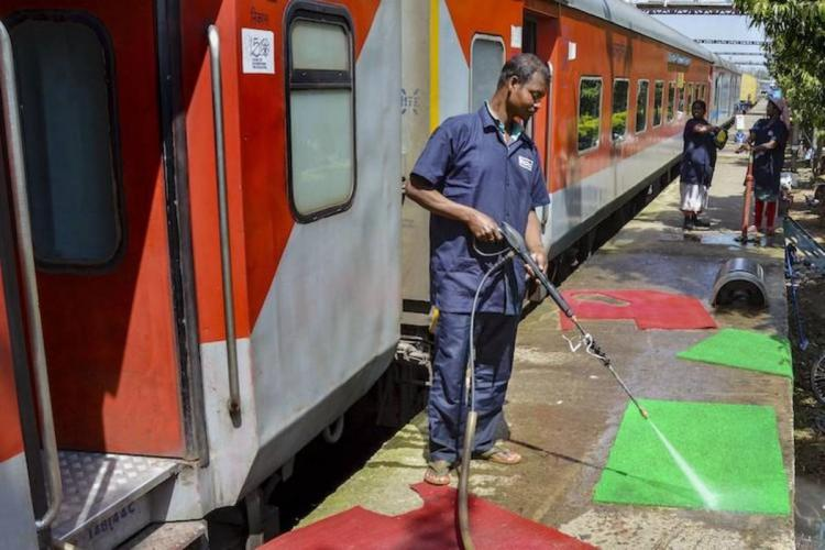Railway workers cleaning the platform next to a train