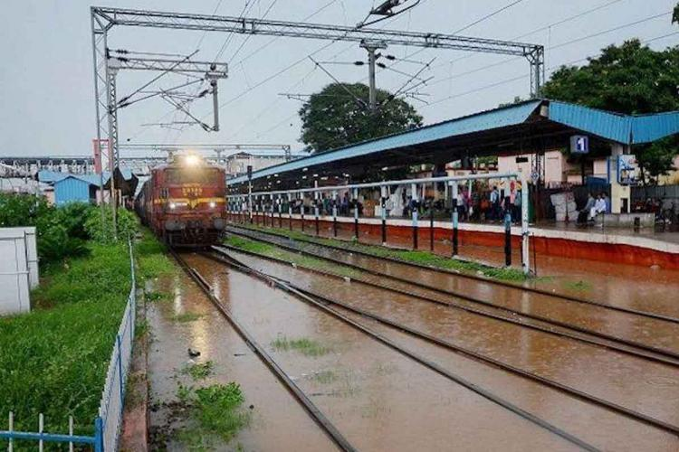 Train passing through flooded railway tracks along by a station