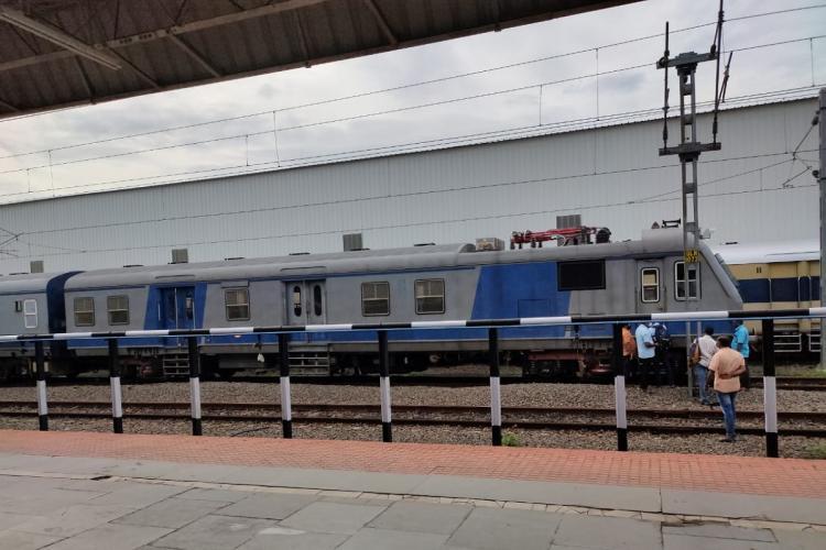 Railway staff near a blue colour train at a railway station