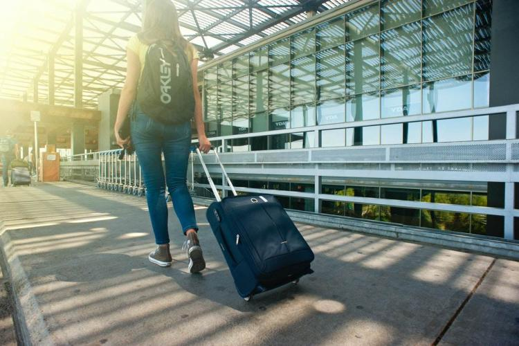 Woman walking in an airport with suitcase