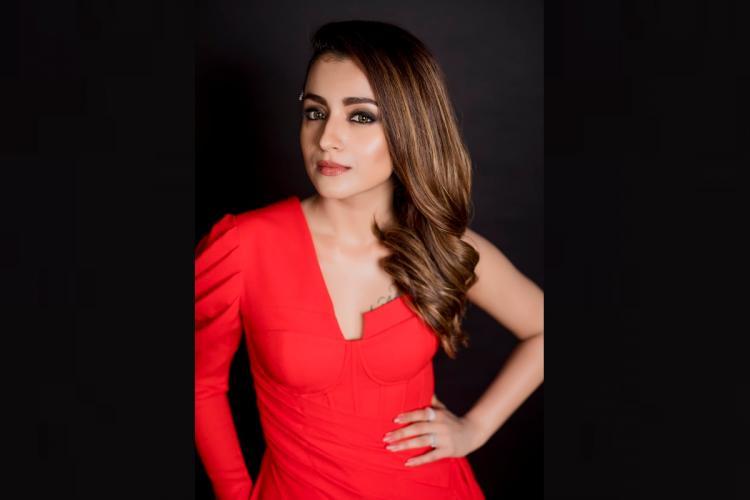 Trisha striking a pose in a red dress