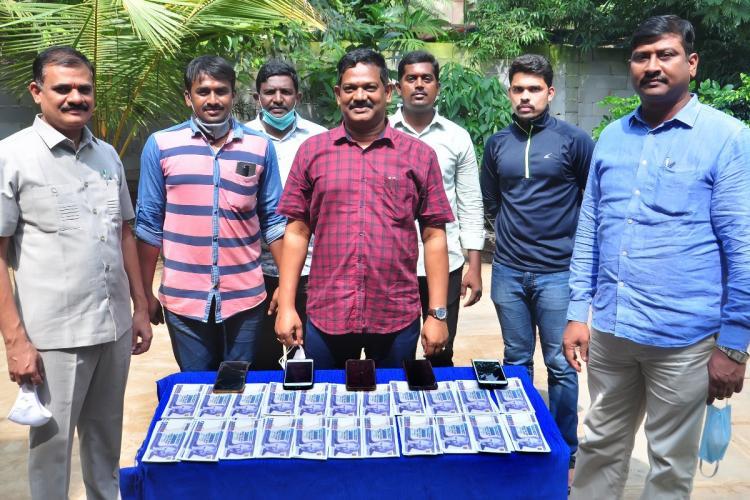 Vijayawada police standing in front of seized Turkish lira notes